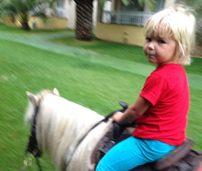 Isla riding a pony.